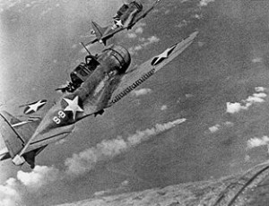 U.S. Douglas SBD-3 Dauntless dive bombers from the USS Hornet mid attack on the burning Japanese cruiser Mikuma